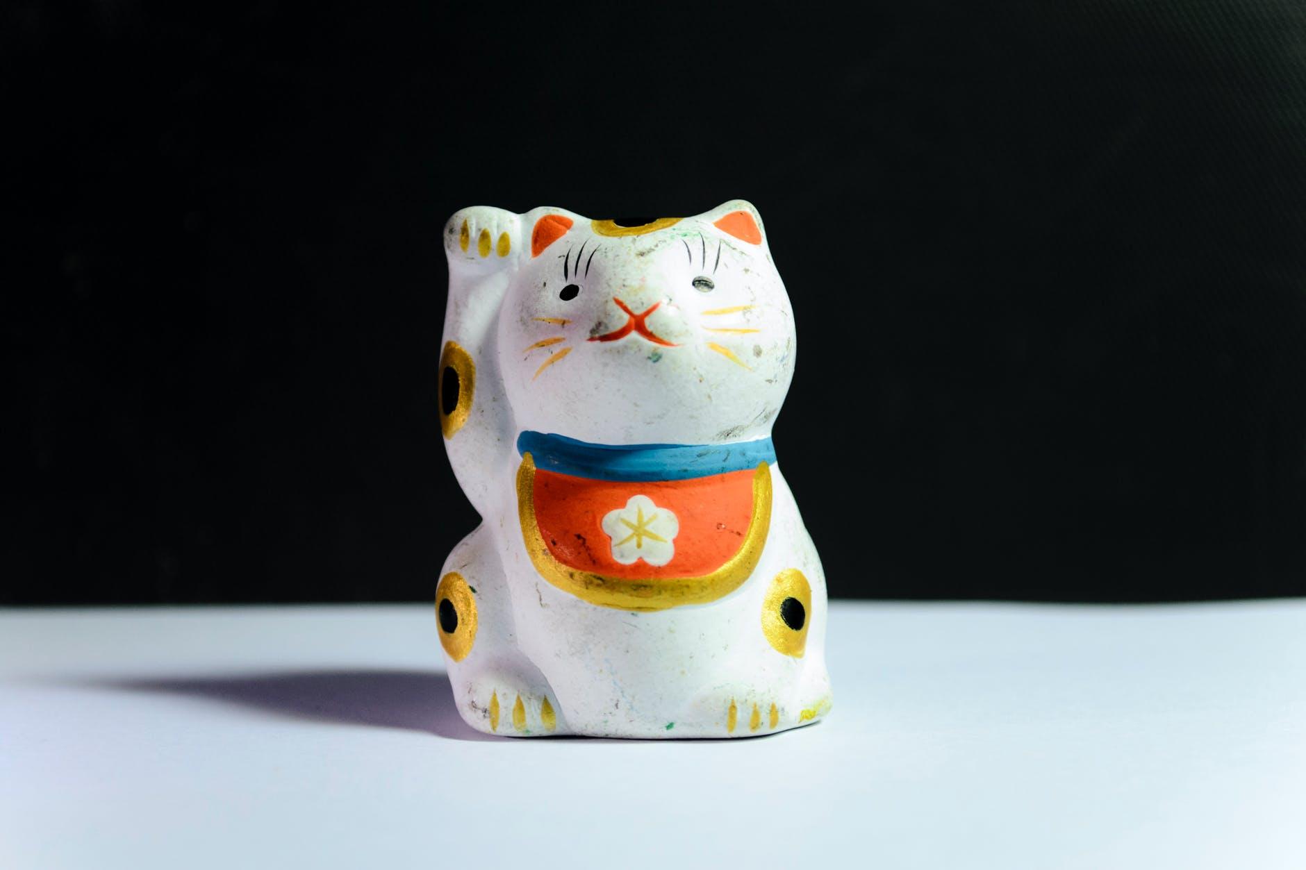 maneki neko figurine on white surface